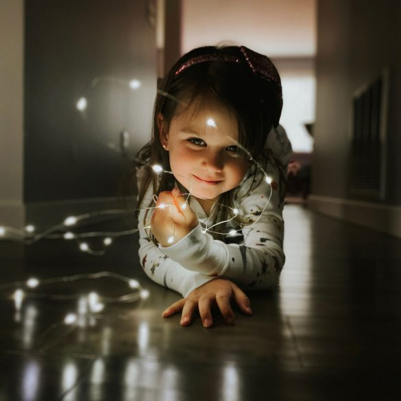 Shot-on-iPhone-holiday-Little-girl-with-string-lights
